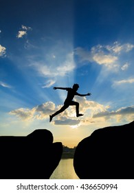 Man jump through the gap between hill.man jumping over cliff on sunset background,silhouette man jumping on sunrise,Business concept idea