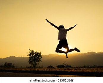 Man jumping against beautiful sunset. Freedom, enjoyment concept.