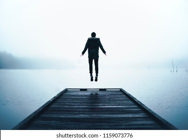 Man Jumping in Air Levitating at End of Wooden Dock Over Big Lake with Thick Layer of Fog and Clouds at Sunrise on Cold Brisk Wet Morning