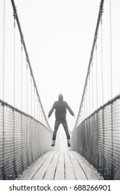 man jumping with arms stretched on suspension bridge during travels