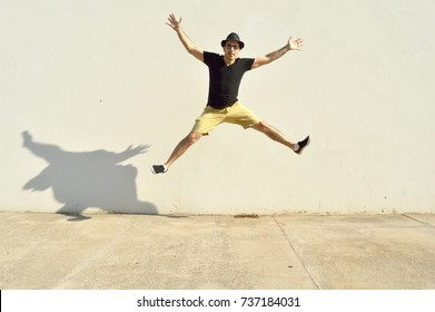 Man jumping with arms wide open against a wall