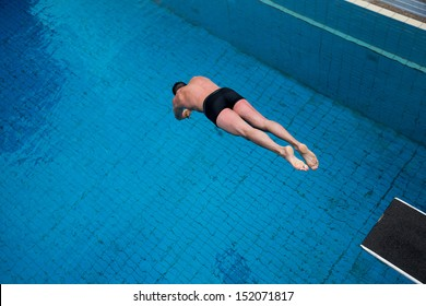 Man jumping from diving board at public swimming pool