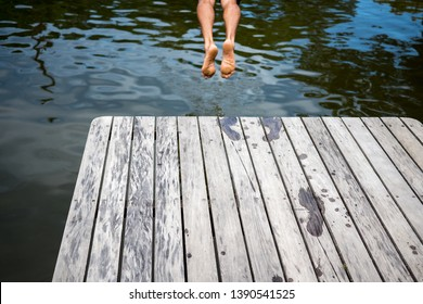 Man jumping from a dock to the water,  visible footprints and legs above the pier.