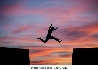 man jumping a gap in sunset sky
