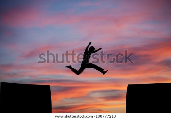 man jumping a gap in sunset sky