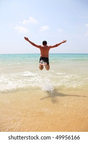 Man jumping high up into the air into the sea