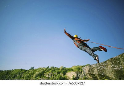 A man is jumping into a canyon.