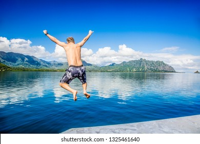 Man jumping into the ocean while on a beautiful scenic Hawaiian vacation. Thrilling and exciting experience. Concept about holiday, success, accomplishment and lifestyle