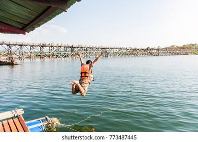 A man jumping into river - Mon Bridge, Sangkhlaburi district, Kanchanaburi, Thailand