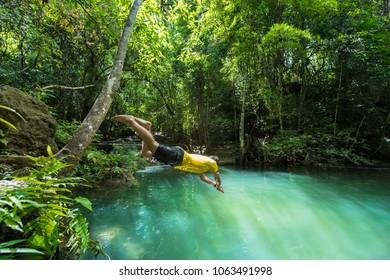 A man jumping into water at Huay Mae Khamin waterfall, Srinakarin National Park, Kanchanaburi, western Thailand