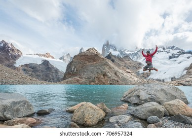 Man jumping for joy at Laguna de Los Tres at the base of Mount Fitz Roy in El Chalten, Argentina in Patagonia