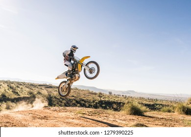 A man jumping with a motocross bike with a sunny background