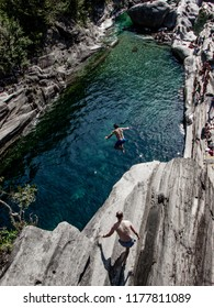 A Man jumping off the Bridge in Valle Verzasca, famous Swiss Location with double arch stone bridge at Ponte dei Salti with waterfall, Lavertezzo, Verzascatal, Canton Tessin – Tecino