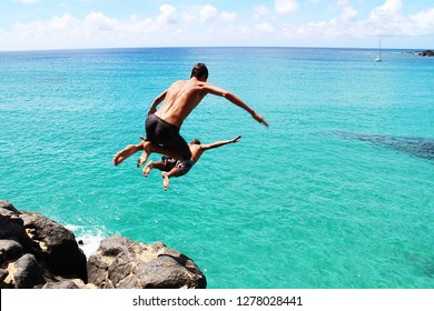 Man jumping off cliff into the ocean. Summer fun lifestyle. Diving cliff ocean