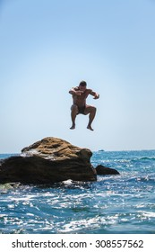 Man jumping off cliff into the sea. Summer fun lifestyle.
