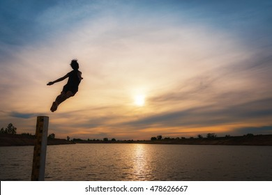 Man jumping off pole into the lake at sunset time, joyful fun lifestyle.