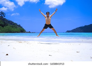 A man is jumping on the beach, Having fun, Summer vacation holiday lifestyle. Happy man jumping freedom on white sand.