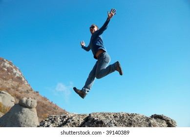 Man jumping on the rocks with landscape background