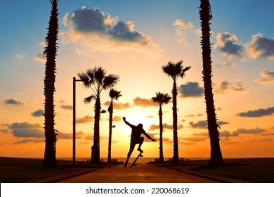 man jumping on skateboard near the ocean in sunset