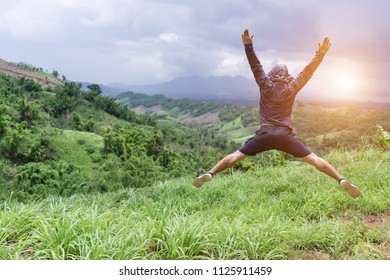 Man jumping on top of mountain hill. Freedom climber on high valley outdoor landscape.