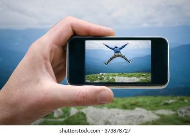 man jumping on top of the mountain, joy, jump, won the top, phone in hand man (photographing the landscape) photographing on the phone, a tourist at the mountain fog. joyful jump