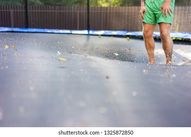 Man jumping on the trampoline outside in the summer