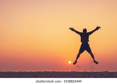 Man jumping on tropical beach with sunset sky and island background. Freedom feel good and travel adventure concept. Vintage tone filter effect color style.