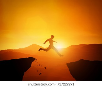 Man jumping from one rock to another. Sunset mountains scenery. Risky challange, winning, brave decision concept.