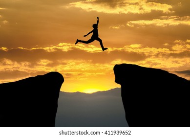 Man jumping over cliff on sunset background,Business concept idea