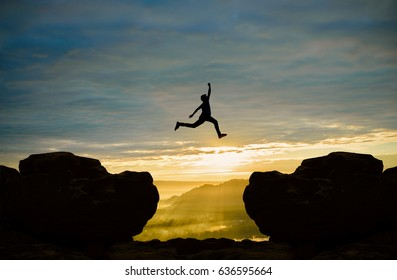 Man jumping over cliff on sunrise background,Business concept idea