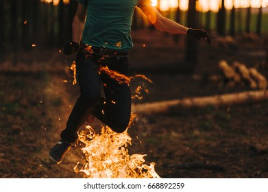 A man is jumping over a fire