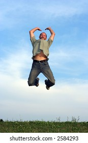 A man jumping over grass with a blue sky behind him