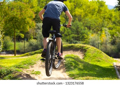 Man is jumping over a hill in a bike parcours with his mountainbike