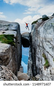 Man jumping over Kjeragbolten Travel in Norway Kjerag mountains extreme vacations adventure tourist crazy travel concept.