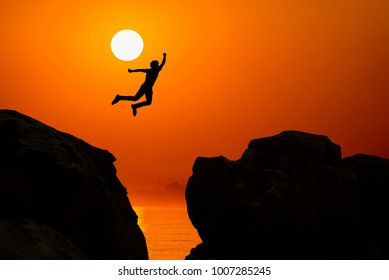 Man jumping over precipice between two rocky mountains at sunrise. Freedom, risk, challenge, success.
