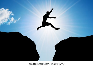 Man jumping over precipice between two rocky mountains at sun light. Freedom, risk, challenge, success.