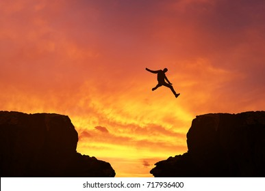 Man jumping over precipice between two rocky mountains at sunset.