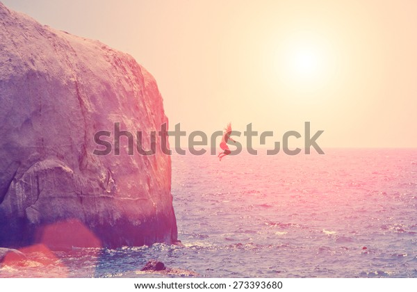 Man jumping from the rock into the sea