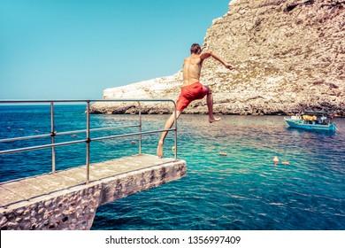 Man jumping to the sea at Xlendi beach at island Gozo, Malta