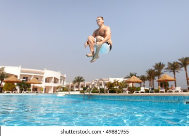 Man jumping in swimming pool.  Low angle view from the swimming pool.