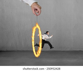 Man jumping through fire circle hand holding with concrete wall background