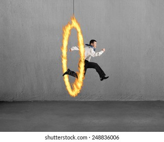 Man jumping through fire hoop with concrete wall background