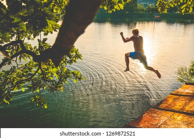 Man jumping to the water in summer in summer evening