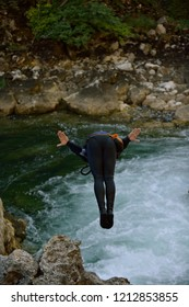 Man jumping in wild river adrenalin sport canyoning