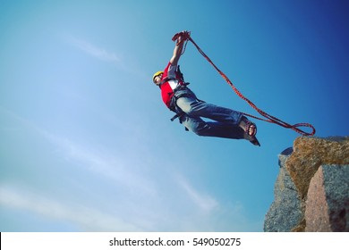 A man jumps from a cliff into the abyss.