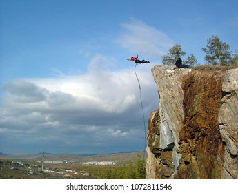 A man jumps from the edge of the cliff into the abyss.