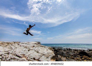 Man jumps from high rock to the sea and blue sky background