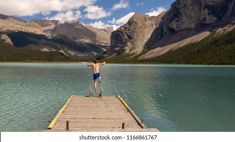 Man jumps into the aqua waters of Maligne Lake. A lake in the Rocky Mountains.