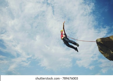 A man jumps into a canyon from a cliff.