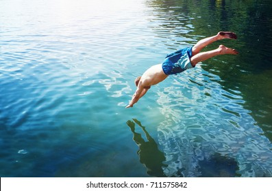 man jumps like fish into the water of the lake, swims, enjoys spending time on summer holidays